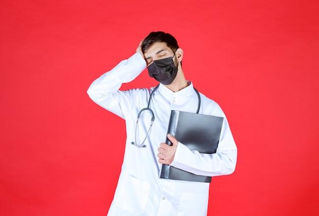 Lekarz w czarnej masce trzyma czarny folder i wygląda na zmęczonego i sennego.
