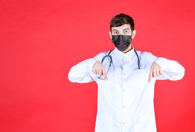 Lekarz w czarnej masce ze stetoskopem na szyi.