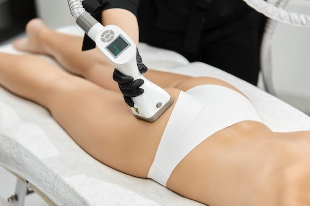 Lekarz w czarnych rękawiczkach masuje perfekcyjną kobiecą dupę z masażerem antycellulitowym