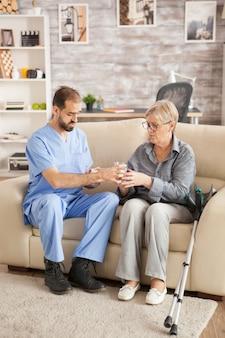 Lekarz w domu opieki pomaga starszej kobiecie wziąć jej lekarstwo.