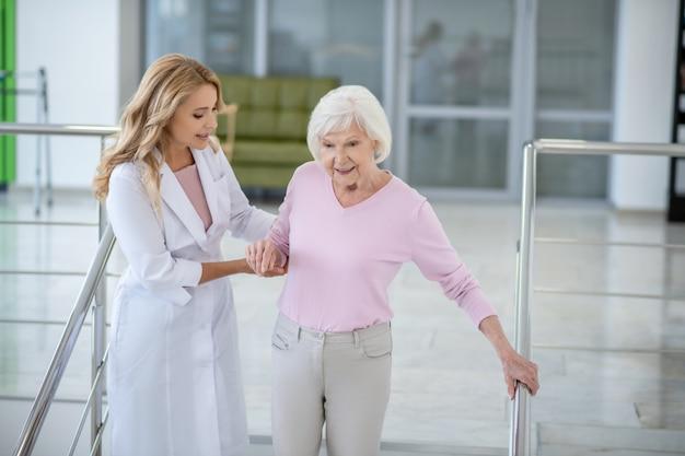 Lekarz w fartuchu laboratoryjnym podtrzymujący pacjenta przy schodach i uśmiechający się do niej