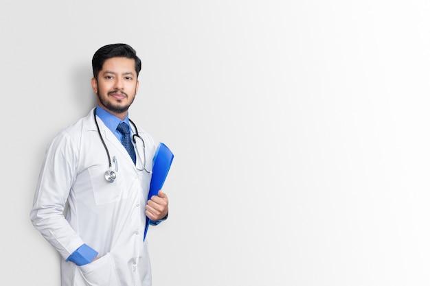 Lekarz w fartuchu posiadający akta pacjenta lub notatki medyczne, patrząc na kamerę, na białym tle na białej ścianie
