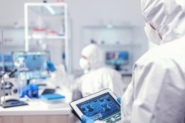 Lekarz w garniturze ppe podczas epidemii koronawirusa pracuje w laboratorium trzymając tablet pc. zespół naukowców zajmujących się opracowywaniem szczepionek z wykorzystaniem zaawansowanej technologii do badania leczenia przeciw c