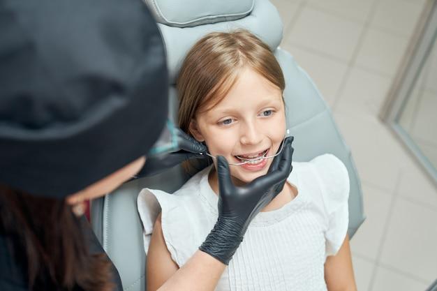 Lekarz w gumowych rękawiczkach diagnozujących zęby.