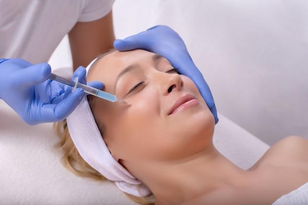 Lekarz w gumowych rękawiczkach wykonujący plastyczną operację twarzy na szczęśliwej młodej kobiecie