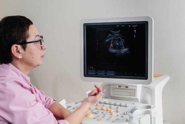 Lekarz w klinice w pobliżu urządzenia do terapii ultradźwiękowej. badanie lekarskie.