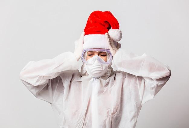 Lekarz w kombinezonie ochronnym i okularach z maską oraz w świątecznym kapeluszu