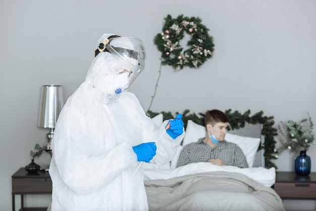 Lekarz w kombinezonie ochronnym ppe przygotowuje się do testu pcr na koronawirusa covid-19 u pacjenta z objawami wirusa