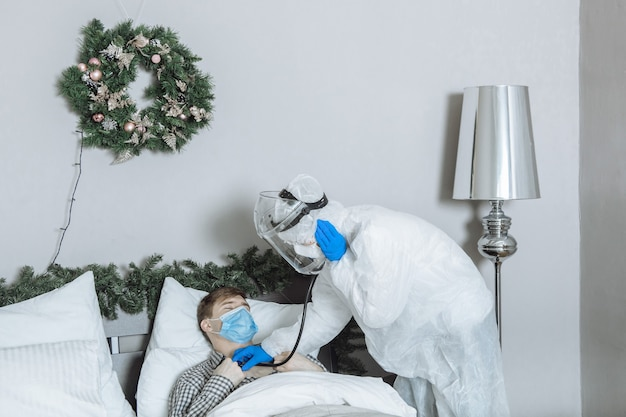 Lekarz w kombinezonie ochronnym ppe słucha w domu pacjenta ze stetoskopem przed nowym rokiem i świętami bożego narodzenia