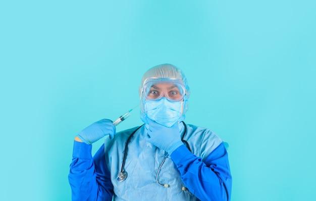 Lekarz w kombinezonie ochronnym ze strzykawką w ręku lekarz w okularach ochronnych i masce medycznej