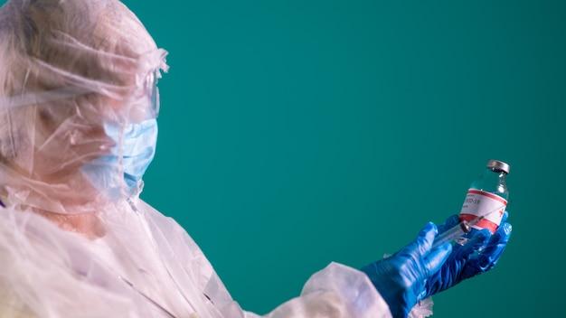 Lekarz w kombinezonie ppe ze stetoskopem trzymającym strzykawkę do szczepionki covid-19