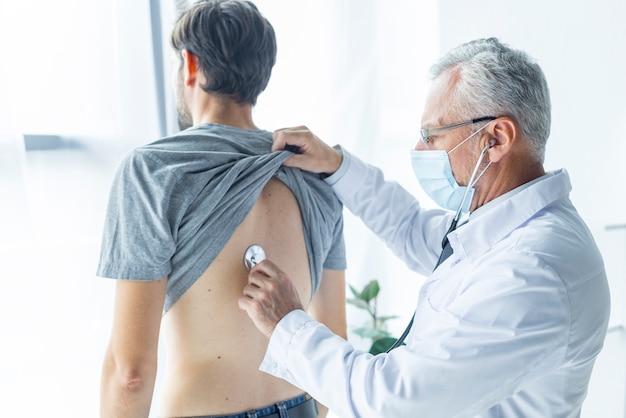Lekarz w masce badając pacjenta