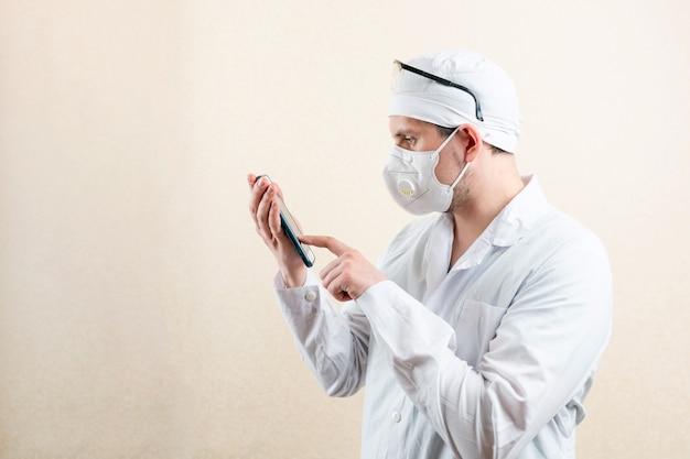Lekarz w masce i okularach z telefonem komórkowym. zdjęcie wysokiej jakości
