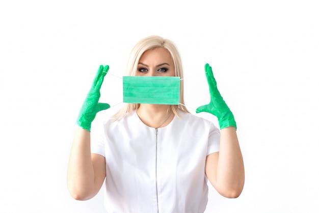 Lekarz w masce medycznej i zielonych gumowych rękawiczkach. wirus, koronawirus. ochrona. sterylny sprzęt dla przemysłu medycznego i kosmetycznego. skopiuj miejsce