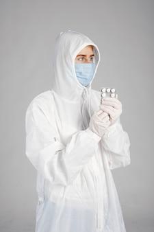 Lekarz w masce medycznej. motyw koronawirusa. pojedynczo na białej ścianie. kobieta z pigułkami.