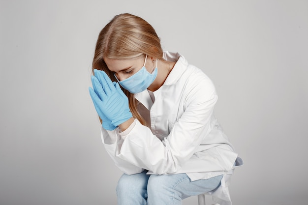 Lekarz w masce medycznej. motyw koronawirusa. pojedynczo na białej ścianie. módlcie się za lekarzy.