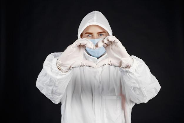 Lekarz w masce medycznej. motyw koronawirusa. pojedynczo na czarnej ścianie. kobieta w kombinezonie ochronnym.