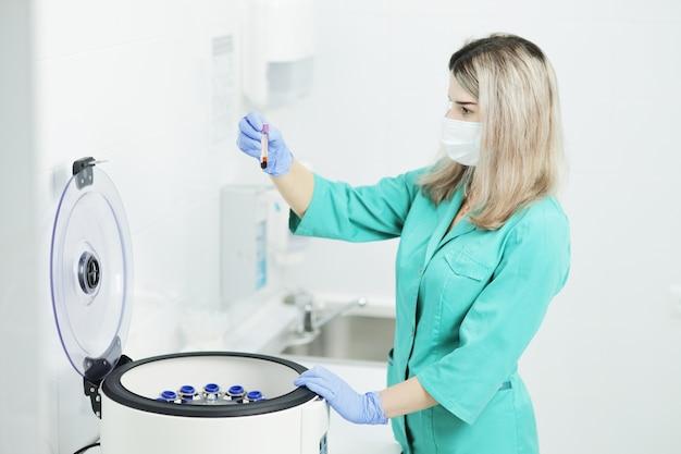 Lekarz w masce medycznej trzyma probówkę krwi w pobliżu wirówki laboratoryjnej