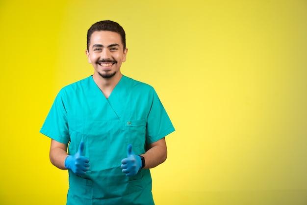 Lekarz w masce munduru i dłoni podejmowania kciuki i uśmiechnięty.
