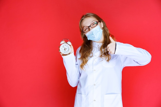 Lekarz w masce na twarz pokazujący zegar oznaczający czas przyjmowania leków.