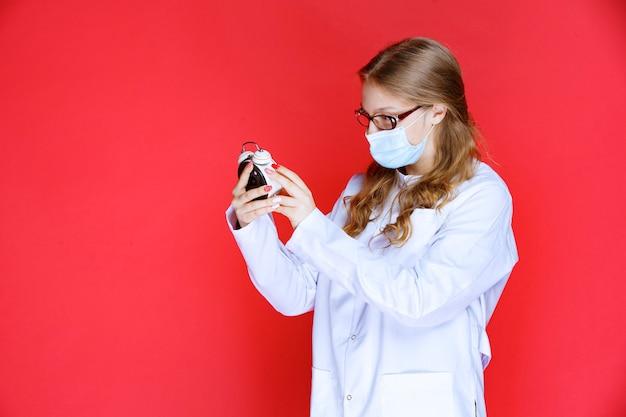 Lekarz w masce na twarz próbuje ustawić budzik.