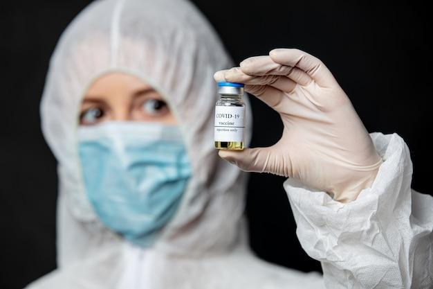 Lekarz w masce na twarz trzyma szczepionkę covid-19 na szczepienie