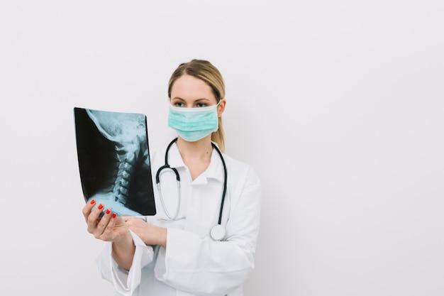 Lekarz w masce rozpatrywania zdjęcie rentgenowskie