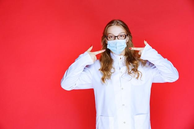 Lekarz w masce, wskazując na siebie.