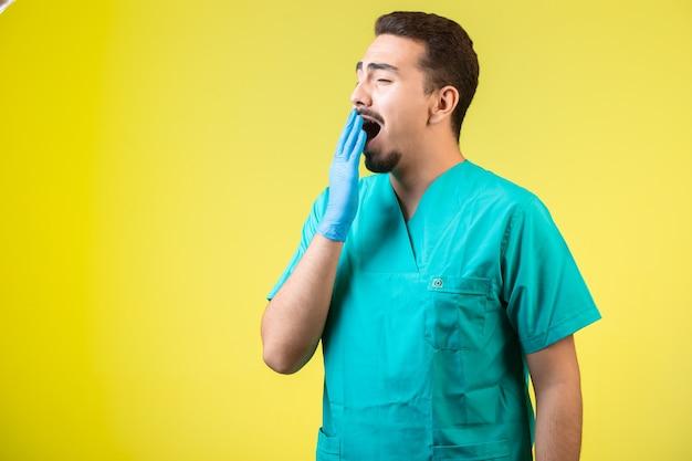 Lekarz w mundurze i masce na dłonie jest zmęczony i chrapie.