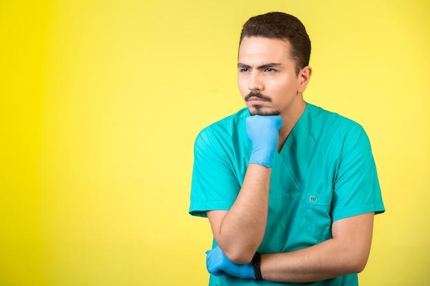 Lekarz w mundurze i masce na ręce, patrząc i zastanawiając się.