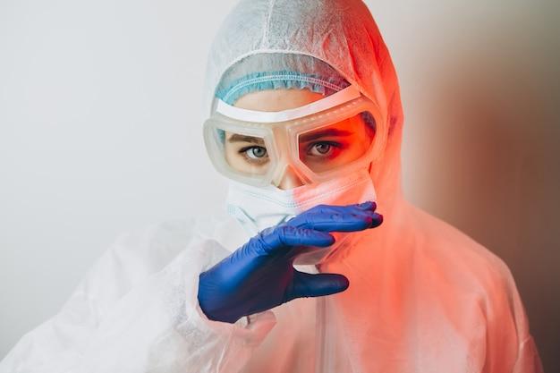 Lekarz w mundurze ochronnym, okulary, rękawiczki na niebieskim tle w świetle neonowym. szczegół portret lekarza w czerwony neon. zmęczony mężczyzna walczy z koronawirusem. covid 19