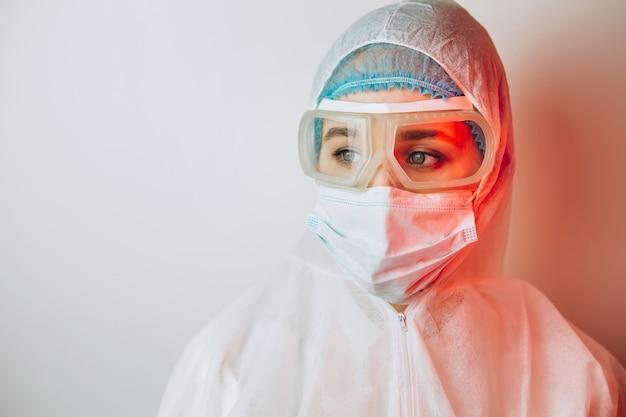 Lekarz w mundurze ochronnym, repertuar, okulary, rękawiczki na niebieskiej ścianie w świetle neonu. zakończenie portret lekarz w czerwonym neonowym. zmęczony mężczyzna walczy z koronawirusem. covid 19