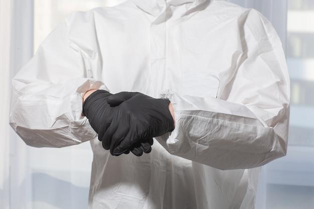 Lekarz w mundurze ppe i rękawiczkach traktuje ręce antyseptycznie z bliska. koronawirus wybuch. koncepcja kwarantanny covid-19. lekarz i opieka medyczna. sprzęt ochrony osobistej zatrzymaj wirusa.