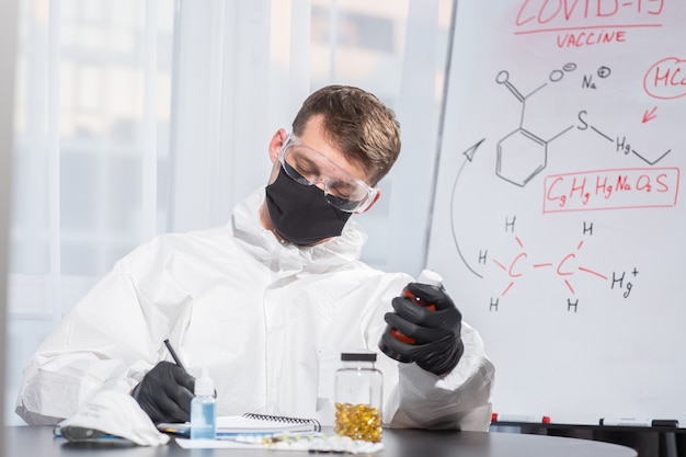 Lekarz w mundurze ppe oblicza formułę wirusa. koronawirus wybuch. koncepcja kwarantanny covid-19. lekarz i opieka medyczna. sprzęt ochrony osobistej . zatrzymać wirusa.