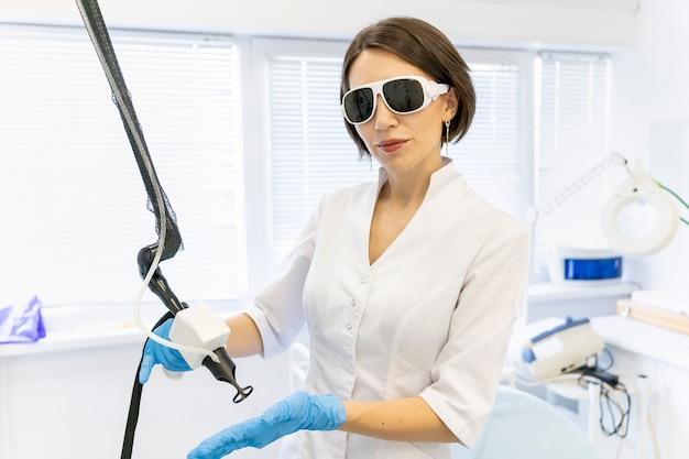 Lekarz w mundurze w okularach ochronnych trzyma laser w dłoniach w rękawiczkach dermatolog