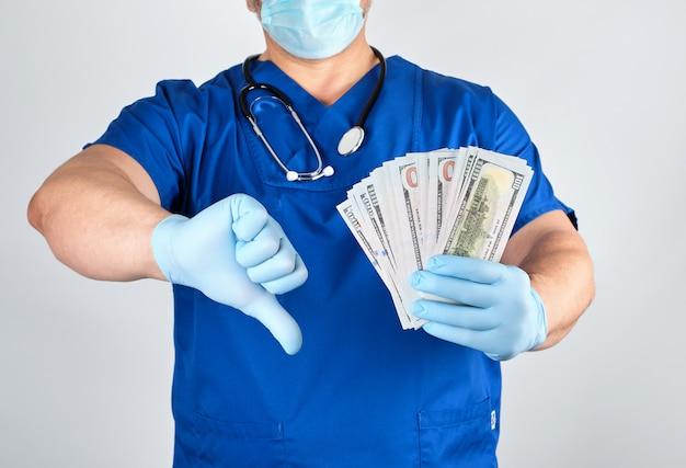 Lekarz w niebieskich rękawicach mundurowych i lateksowych trzyma jedną rękę dużo pieniędzy, z drugiej strony pokazuje zły gest