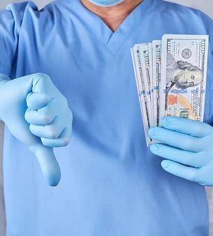 Lekarz w niebieskich rękawiczkach mundurowych i lateksowych trzyma jedną rękę dużo pieniędzy