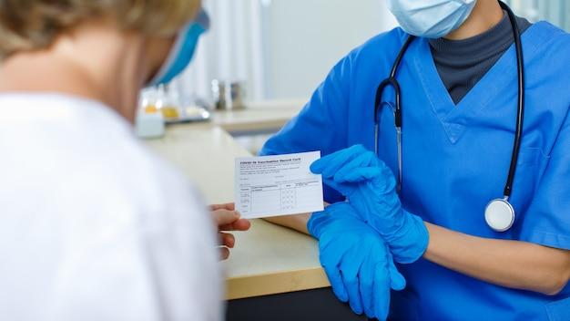 Lekarz w niebieskiej szpitalnej jednolitej masce na twarz i gumowych rękawiczkach ze stetoskopem wysyła i wyjaśnia zaświadczenie karty szczepień przeciwko covid-19 pacjentce rasy kaukaskiej na niewyraźnym pierwszym planie.