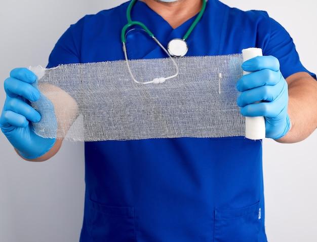 Lekarz w niebieskim mundurze i lateksowych rękawiczkach trzyma rolkę białego bandaża do opatrywania ran z gazy