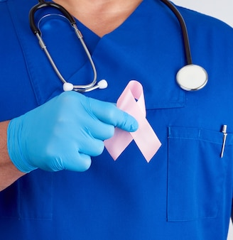Lekarz w niebieskim mundurze i sterylnych rękawicach lateksowych trzyma różową wstążkę