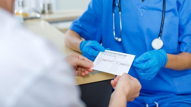 Lekarz w niebieskim mundurze szpitalnym i gumowych rękawiczkach ze stetoskopem wysyła pokaz i wyjaśnia pacjentowi paszport z karty szczepień przeciwko covid-19, aby mógł przeczytać i zrozumieć zamazany pierwszy plan.