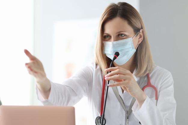 Lekarz w ochronnej masce medycznej mówi do mikrofonu. prezentacja na koncepcji konferencji