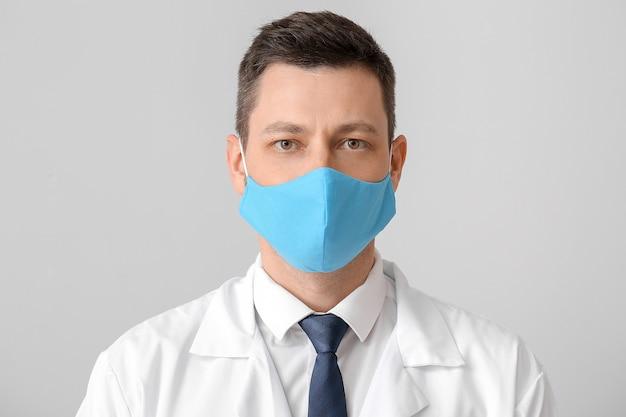 Lekarz w ochronnej masce medycznej na szarej powierzchni