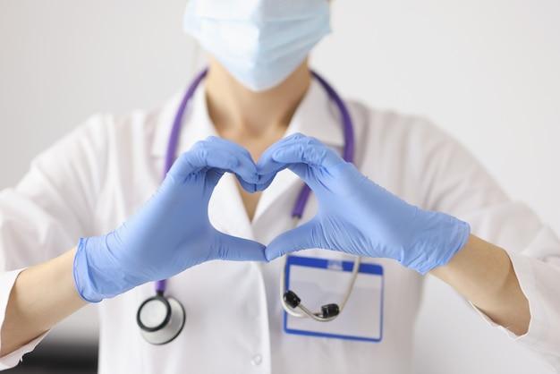 Lekarz w ochronnej masce medycznej pokazuje serce rękami