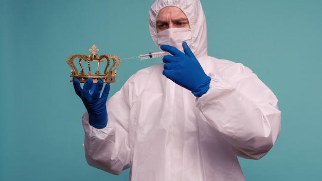 Lekarz w ochronnym kombinezonie i masce wykonuje zastrzyk w koronę. koncepcja ochrony przed koronowirusem w chinach. - wizerunek