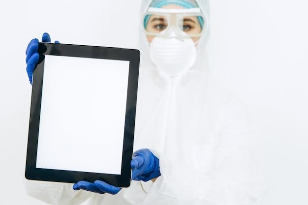 Lekarz w odzieży ochronnej, respiratorze, okularach, rękawiczkach trzyma tabletkę. lekarze namawiali do pozostania w domu podczas epidemii koronawirusa. covid-19