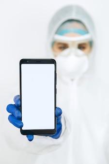 Lekarz w odzieży ochronnej, respiratorze, okularach, rękawiczkach trzyma telefon. lekarze namawiali do pozostania w domu podczas epidemii koronawirusa. covid-19