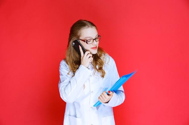 Lekarz w okularach i trzymający niebieski folder rozmawia przez telefon.