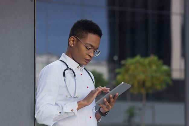 Lekarz w pobliżu kliniki trzyma w ręku tablet, czyta wiadomości afroamerykanin poważnie studiuje informacje z internetu, w celu konsultacji online z pacjentami