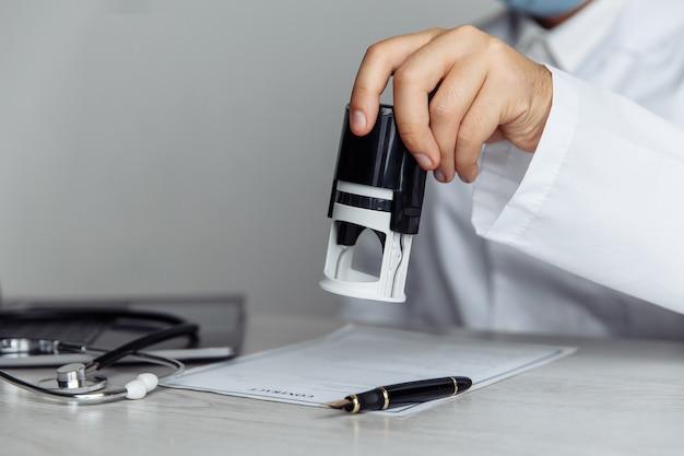 Lekarz w publicznym gabinecie lekarskim stempluje dokument medyczny. koncepcja medycyny i opieki zdrowotnej